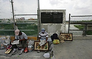 Photo by Alex Jones..Vendors wait for customers in the middle of the Hidalgo - Reynosa international bridge on June 20, as a dirty sign above them marks the international boundary between the US and Mexico.
