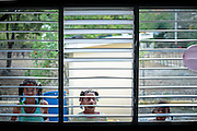 Three girls look from outside of the school window in Azua<br />
