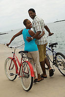 Couple walking with bicycles on beach (portrait)