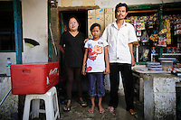 Ibu Hamriani with her husband Bapak Agus and daughter Nurlina at the Jongaya leprosy settlement, Makassar, Sulawesi, Indonesia. Ibu Hamriani, 39, moved to the Jongaya leprosy settlement 13 years ago.  She discovered she had leprosy much earlier but left the infection untreated until too late and now has problems with her toes and fingers.  She is married to Bapak Agus, 43, and they have one daughter together, Nurlina, 11, who was born in the house where she now runs a small kiosk selling general goods.