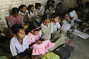 IND.MWdrv04.058.x..Seema Yadav, in pink, reading in her school classroom, wasn't yet born when the Material World family portrait was taken in 1994. Ahraura Village, Uttar Pradesh, India. Revisit with the family, 2004. The Yadavs were India's participants in Material World: A Global Family Portrait, 1994 (pages: 64-65), for which they took all of their possessions out of their house for a family-and-possessions-portrait. Child, Children, Education..