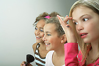 Girls standing side by side putting on make-up fixing hair