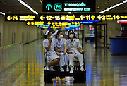 Thai nurses take a ride after checking passengers arriving from Hong Kong at Bangkok's International Airport, in an effort to prevent new cases of the SARS virus in Thailand . All travelers arriving from high-risk countries in the Asia-Pacific region are being carefully monitored. Thailandís Deputy Prime Minister Somkid Jatusripitak said Sars has cost the tourism industry about 30 billion baht so far. Mr Somkid said the tourism authority attributed the loss to the disease spreading in nearby countries, rather than in Thailand, thereby scaring tourists.
