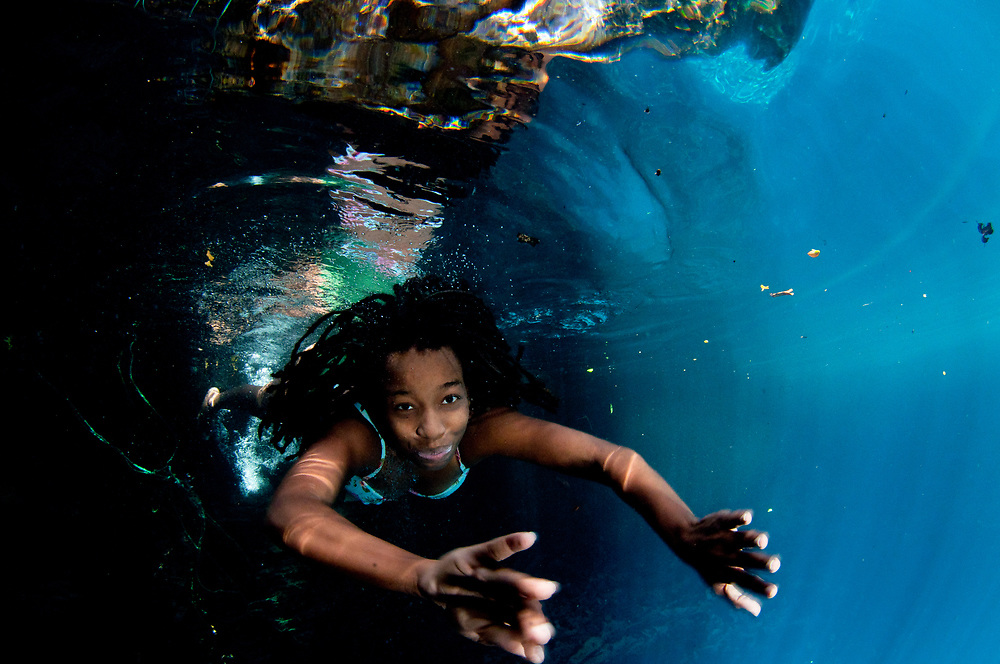 Bahamian activist Adell Farquharson dives in to a blue hole. Getting protections for the blue holes is tricky partly because the land around many of them are owned by many different parties.