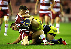 Wigan Warriors' John Bateman (left) is tackled by Wakefield Trinity's Tyler Randell during the Betfred Super League Super 8's match at the DW Stadium, Wigan.