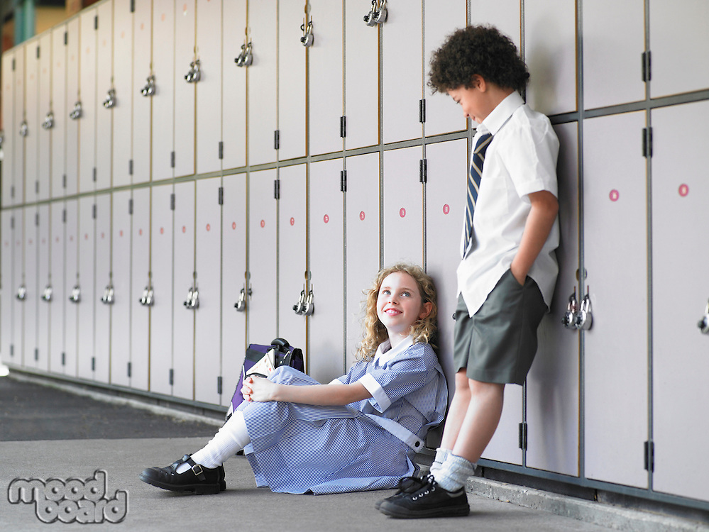 Two elementary school students waiting by school lockers