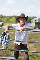 middle aged cowboy with a goatee leaning on a fence