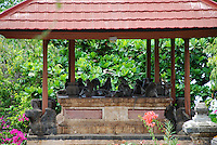 Monkeys sitting in the shade of the Polaki temple in Bali, Indonesia.