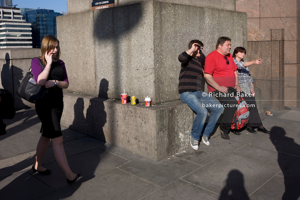 With three drinks cartons sit propped up on a stone ledge, three tourists rest around its corner, surrouded by commuters