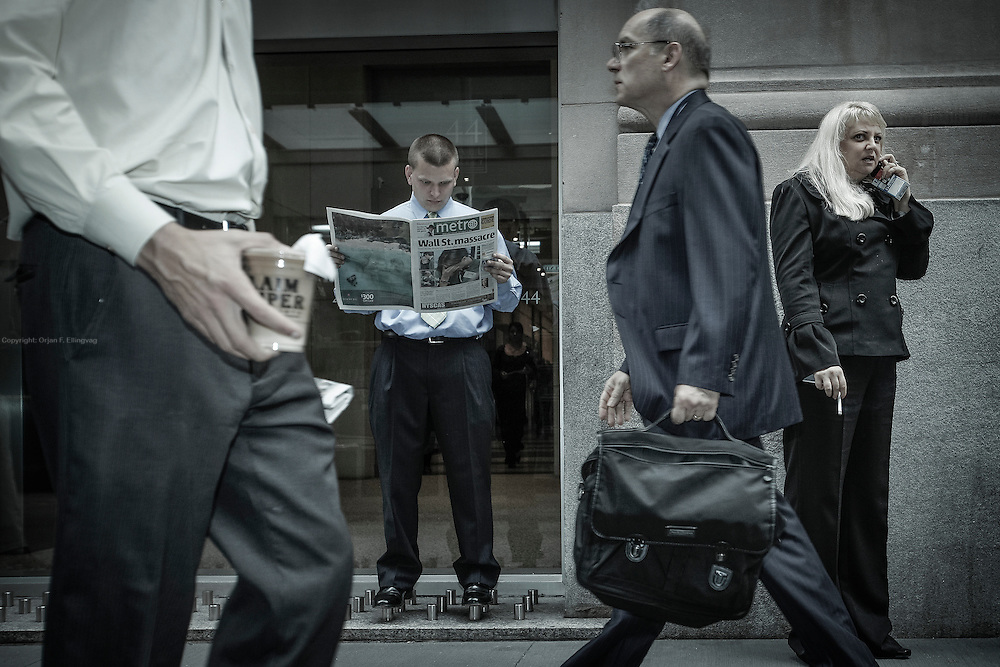 "In days of financial turmoil, a Wall Street trader balances on pavement obstructions while reading the Metro paper. The front page bears the title ""Wall Street Massacre"". The image was taken the day after President Obama urged the financial industry to overhaul its system and accept regulatory changes."
