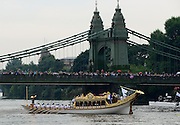 © Licensed to London News Pictures. 27/07/2012. Hammersmith, UK Crowds line the bridge as the rowboat Gloriana lowers the Olympic Flag on its stern to allow it to pass under Hammersmith Bridge. The boat that lead the Royal Jubilee, The Gloriana, carries the Olympic flame on The Thames River towards Central London today through Hammersmith Bridge on it's way to the Olympic Opening Ceremony that takes place tonight at 20:12 27th July 2012. Photo credit : Stephen Simpson/LNP