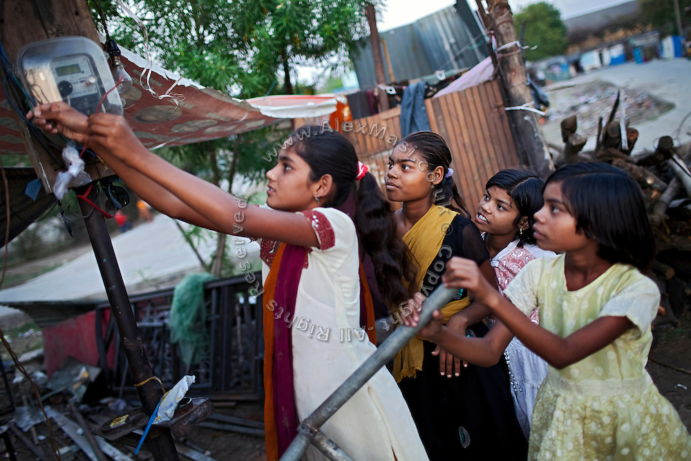 (right to left) Jyoti, 11, Poonam, 10, and their older sister Arti, 16, are warily observing their friend and neighbour, Pooja, 16, connecting electric cables near Poonam's newly built home in Oriya Basti, one of the water-contaminated colonies in Bhopal, central India, near the abandoned Union Carbide (now DOW Chemical) industrial complex, site of the infamous '1984 Gas Disaster'.