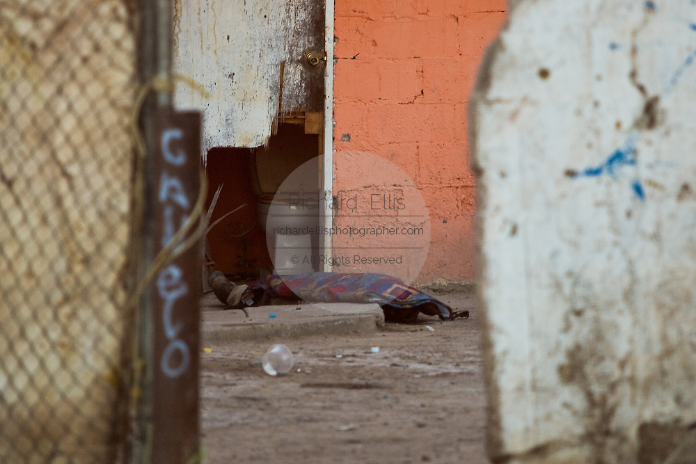 The body of a slain drug gang member lays in the backyard of a home in a slum in Juarez, Mexico January 14, 2009 where four people were killed in a shoot out between rival gangs.The shooting, believed linked to the ongoing drug war which has already claimed more than 40 people since the start of the year. More than 1600 people were killed in Juarez in 2008, making Juarez the most violent city in Mexico.    (Photo by Richard Ellis)