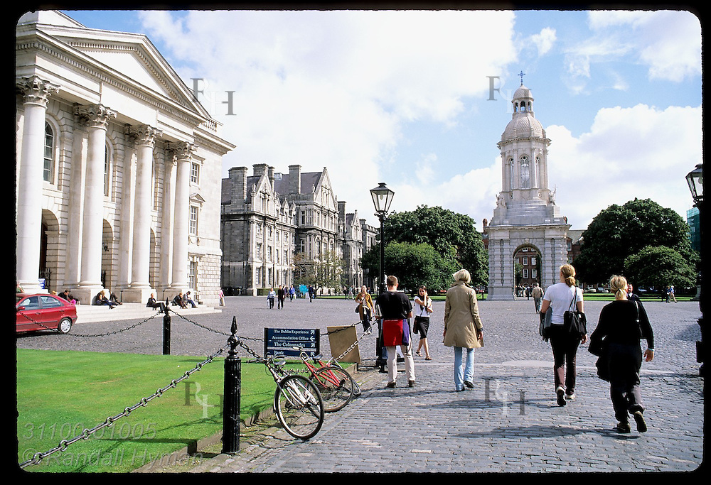 Students walk across cobblestone plaza inside Trinity College campus near entrance; Dublin, Ireland.