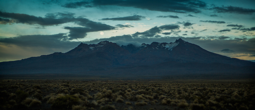Mt Ruapehu at dawn as seen from Desert Road, New Zealand, while the moon sets behind the mountain.