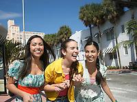 Three teenage girls (16-17) walking on street and laughing