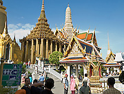 Visitors explore the visually rich Temple of the Emerald Buddha (Wat Phra Kaew) in Bangkok, Thailand. The cylindrical dark gold building with many columns (on the left) is the Phra Mondop building, built by King Rama I in order to house the revised edition of the Buddhist Canon. The walls of the Phra Mondop are covered in green mirrored tiles inlaid with gold medallions depicting Buddha. The base of the walls are lined with two rows of small gilded guardian angels, each one slightly different. At the four corners of the Phra Mondop are stone Buddhas carved in the ninth century Javanese style. Sixteen twelve-cornered columns support the intricate multi-tier roof.