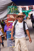 A parakeet vendor carries cages showing his wares at the Sunday market in Tlacolula de Matamoros, Mexico. The regional street market draws thousands of sellers and shoppers from throughout the Valles Centrales de Oaxaca.