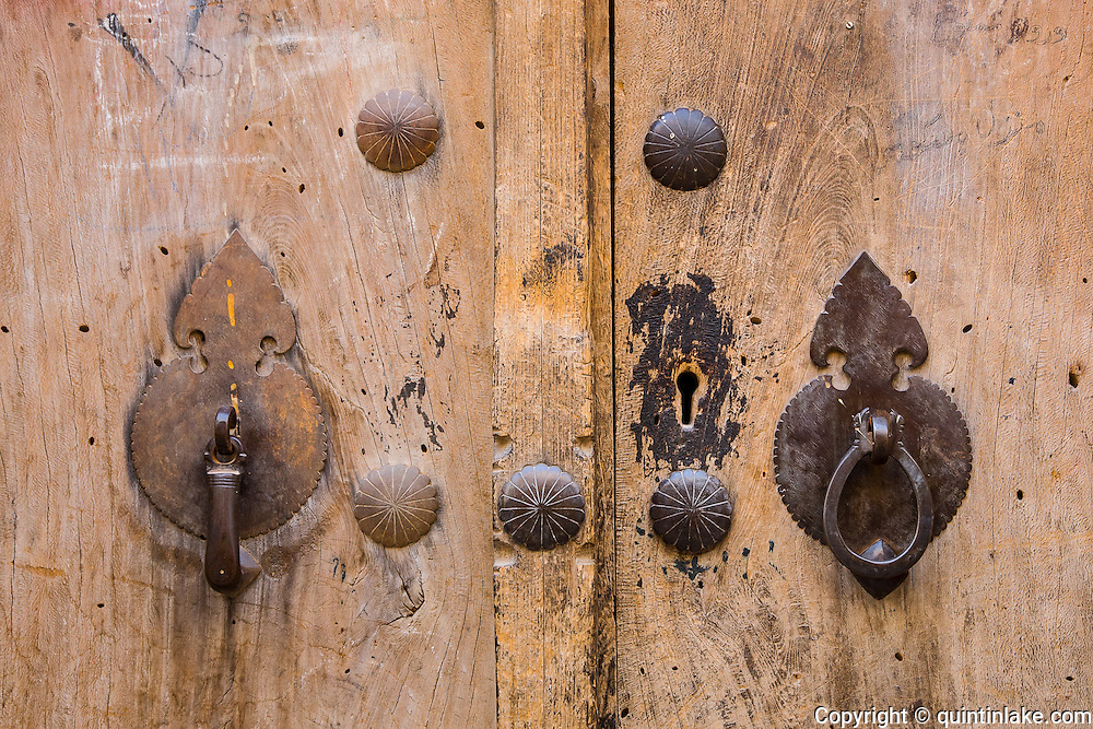 His and hers door knockers, Yazd, Iran. The masculine door knocker is rigid and heavy that makes a strong sound. People inside the house wil be informed that a man is behind the door. The feminine door knocker is curly and ring like and makes a lighter sound. It informs the people inside the house that a woman is behind the door. This system is in place due to the Islamic custom that women should be private from men except their intimate ones.
