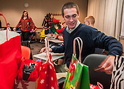 Patrick Burke, freshmen, reaches for a pile of presents bought for Secret Santa during The College of Business Honors Program's Christmas party in Copeland Hall on Wednesday, December 5, 2012.