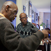 Mr. Johnson, right, and caretaker Mr. Griffin look at old photographs on the wall. John E. Johnson, who is not eligible for medicaid, receives services for 12 hours per week through Illinois' Community Care Program. Johnson worries his services will be cut if the state transition seniors like him to a new program. The state employs Reggie Griffin to help Johnson with daily chores so he is able to stay in his home, as opposed to going to an nursing home. <br /> Photography by Jose More