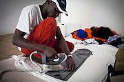 Un ragazzo stira i propri vestiti. Interno ex palazzine olimpiche.