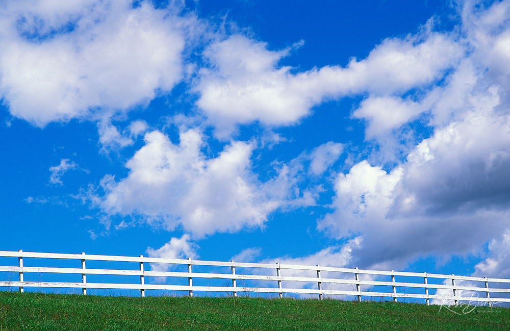 Clouds in blue sky above white fence and green grass in upper Ojai Valley, Ojai, California.
