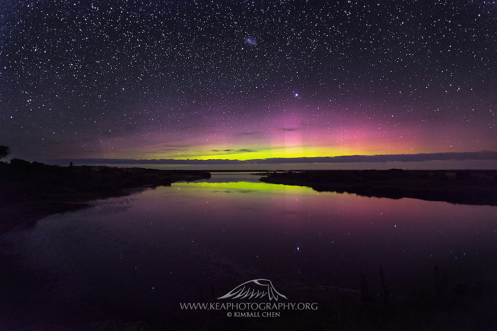 The Aurora Australis reflects upon the still waters of Waituna Lagoon, in Southland, New Zealand.