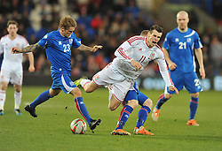 Aron Einar Gunnarson (Cardiff City) of Iceland fouls Gareth Bale of Wales (Real Madrid) - Photo mandatory by-line: Alex James/JMP - Tel: Mobile: 07966 386802 05/03/2014 - SPORT - FOOTBALL - Cardiff - Cardiff City Stadium - Wales v Iceland - International Friendly