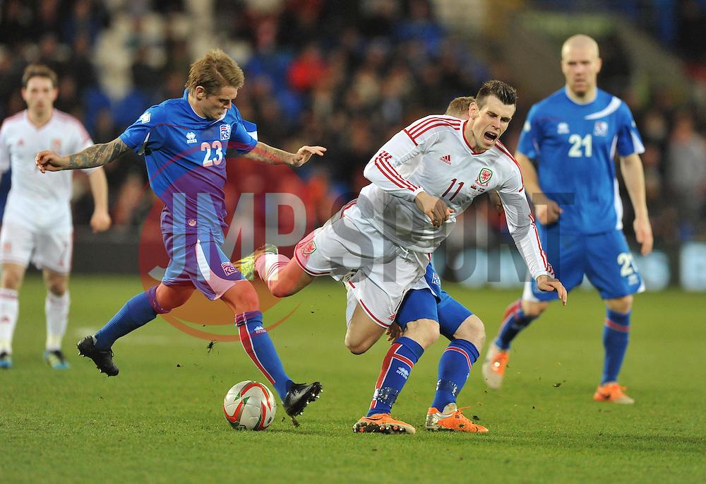 Aron Einar Gunnarson (Cardiff City) of Iceland fouls Gareth Bale of Wales (Real Madrid) - Photo mandatory by-line: Alex James/JMP - Tel: Mobile: 07966 386802 05/03/2014 - SPORT - FOOTBALL - Cardiff - Cardiff City Stadium - Wales v Iceland - International Friendly