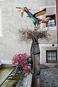 "Public art: a bird on nest holds a fish in Pontresina, Upper Engadine, Graubünden (Grisons) canton, Switzerland, the Alps, Europe. The Swiss valley of Engadine translates as the ""garden of the En (or Inn) River"" (Engadin in German, Engiadina in Romansh, Engadina in Italian)."