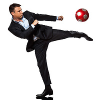 one caucasian business man playing kicking soccer ball in studio isolated on white background