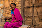 Women wearing their traditional sarees and silver jewellery. Jaisalmer. Rajasthan, INDIA<br /> Heavy ankle bracelets are common as well as nose rings and silver bangles.<br /> Founded in 1156 Jaisalmer grew to be a major staging post on the trade route across the forbidding Thar desert from India to the west. It is known as the Golden City as the fort and town's buildings are built from the local yellow sandstone. The bustling narrow streets are lined with tradesmen selling their wares. Many of the smalll shops are occupied by descendents of the original owners. There are many exceptional Havelis (mansions of rich merchants - exquistely carved) both in the fort and the old walled town.
