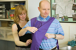 Day Service Officer helping a service user put on an apron to protect clothes during an arts and crafts activity,