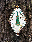 A metal trail marker show the way to go to follow the Pacific Crest Trail in Oregon. Trail markers can sometimes be very common, posted every few miles, others times it can be a long time before seeing them.