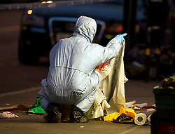 © Licensed to London News Pictures. 10/07/2015. London, UK. A forensics officer holding bloodied clothing. Police and forensics forensics at the scene of a double shooting on Lordship Lame in Wood Green, north London in which a man has died and a woman is currently being treated in hospital.  Photo credit: Ben Cawthra/LNP
