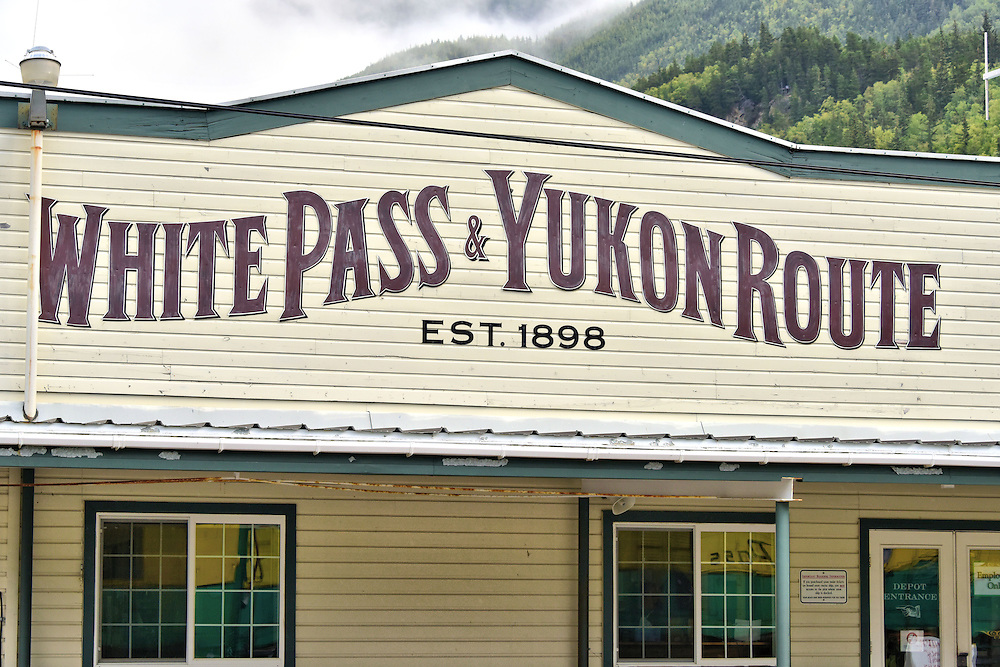 White Pass & Yukon Route Marquee in Skagway, Alaska<br /> On August 16, 1896, gold was discovered in the Klondike region of the Yukon and soon 100,000 prospectors surged towards Skagway, Alaska, as part of the Klondike Gold Rush. When this marquee was first painted on the train station in 1898, only 4,000 had harvested any gold.  By the time the train route was finished in 1900, the rush was just about over and most of the gold diggers who survived had gone home penniless.  Anecdotally, my great grandfather was one of the unlucky ones.