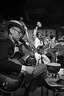 "Tokyo, Japan:  This is ""Tokyo Kan Kan Rhythm"", a house band that plays 1920s to 1940s style ragtime, dixieland jazz, blues and tin-pan alley songs at Music Bar RPM. This bar is located in the hip and trendy Tokyo neighborhood of Shimokitazawa. The director of this band is Keita Sugiyama, the lead singer, banjo/guitar/ukulele player. He is seen in the white pinstripe suit and straw hat (center), performing on his birthday. Sugiyama is also the manager of Music Bar RPM, a cool live music venue with red walls and regular concerts. The Shimokitazawa neighborhood of Tokyo is known for it's tiny bars, pubs, cafes, theaters, galleries, coffee houses and live music venues. Dec. 10, 2014. Photo by Torin Boyd.<br />