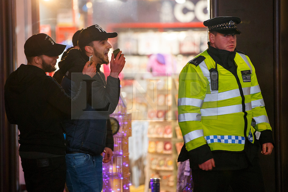 © Licensed to London News Pictures. 01/01/2017. London, UK. A police officer is being filmed by angry revellers as revellers celebrate the New Year in central London during the first hours of 2017 on January 1. Photo credit: Tolga Akmen/LNP