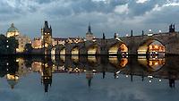 Die Karlsbrücke in Prag bei Nacht mit Spiegelung in der Moldau. Die Karlsbrücke ist eine im 14. Jahrhundert errichtete, historisch bedeutsame Brücke über die Moldau in Prag.