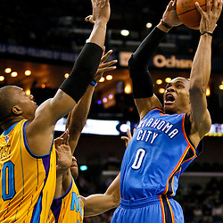 December 10, 2010; New Orleans, LA, USA; Oklahoma City Thunder guard Russell Westbrook (0) shoots over New Orleans Hornets power forward David West (30) during the first half at the New Orleans Arena.  Mandatory Credit: Derick E. Hingle-US PRESSWIRE