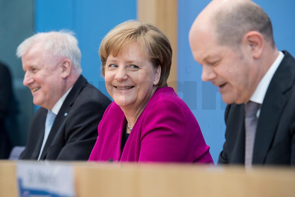 12 MAR 2018, BERLIN/GERMANY:<br /> Horst Seehofer (L), CSU, desig. Bundesinnenminister, Angela Merkel (M), CDU, Bundeskanzlerin, und Olaf Scholz (R), SPD, desig. Bundesfinanzminister, waehrend einer Pressekonferenz zum Koalitionsvertrag der CDU/CSU und SPD, Bundespressekonferenz<br /> IMAGE: 20180312-01-014<br /> KEYWORDS: freundlich