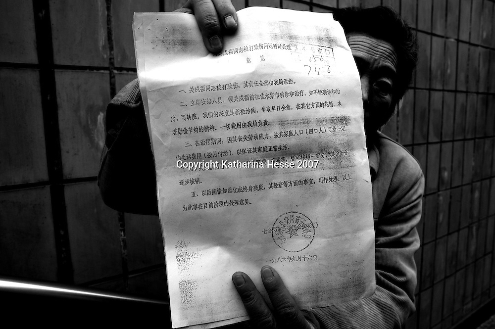 BEIJING, DECEMBER-22:  a woman shows a court verdict issued in 1986 that promises medical recompensation that has never been paid...  ..Hundreds of thousands of Chinese have descended upon Beijing in the past decades hoping to get the attention of higher authorities for cival law cases reaching from work accidents, violence against family members, murder,  money extorsion and which in the majority reveal a corrupt rural legal system...The tradition of  appealing to higher authorities  in the capital reaches back to imperial times . In Beijing , petitioners villages where people would congregate in cheap housing, outside the city centre were common. These days though, petitioners increasingly face tremendous obstacles to get heard : provincial as well as undercover police try to stop petitioners from going to the National Petition offices to file law suites . If caught, they are briefly sent to an unoffical detention centre where they wait for the train ride back to the province.  In addition  the number of villages has been reduced significantly as the preparations for the 2008 Olympics progress. Many fear they will be all gone  by summer 2008. ..