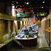 The tops of the massive turbines generating electricity from the water flowing through the Hoover Dam and into the Colorado River. The turbines stand about 30 feet tall from the ground in this room with another 40 feet below this level. The room is about 650 feet long. At top can be seen one of the massive cranes that can lift 300 tons.