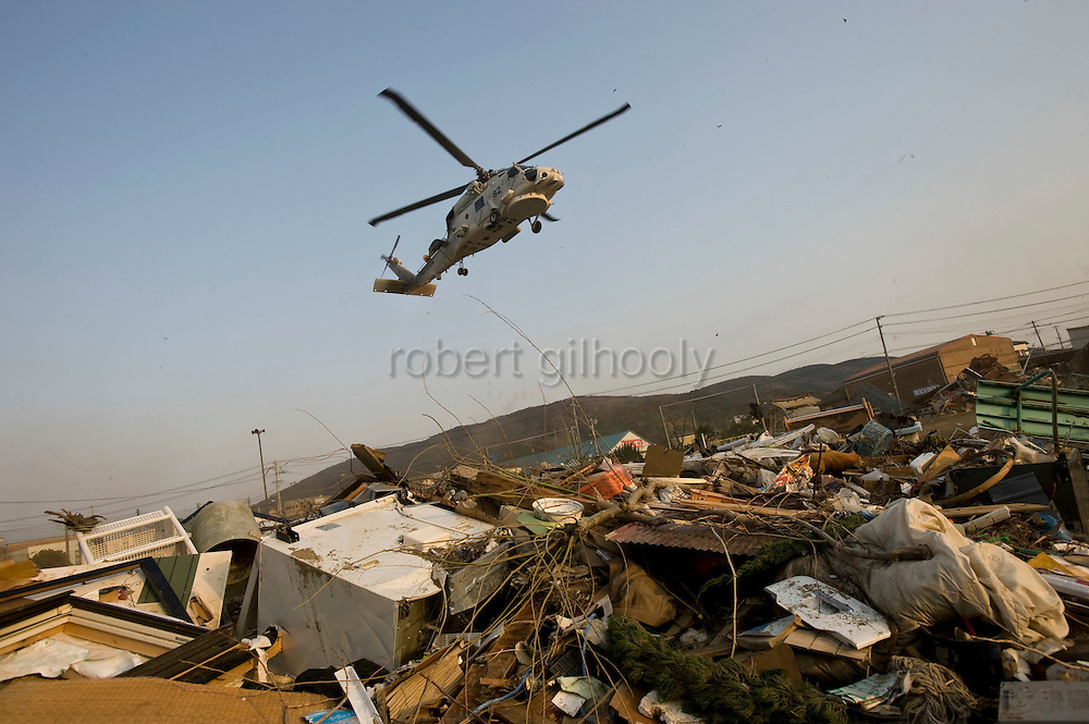 A helicopter carrying emergency medical supplies lands in the playground of Watanoha elementary school, which currently houses over 1,000 residents made homeless by the March 11 quake and tsunamis  in Ishinomaki, Japan on 19 March, 2011.  Photographer: Robert Gilhooly