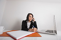 Businesswomen using cell phone while writing notes from laptop at office desk