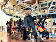 Garden City, New York, USA. March 9, 2019. At right, GARY FARKASH, Baldwin Historical Society President rides Nunley's Carousel with Baldwin organization members and local elected officials during Unveiling Ceremony for artist Michael White mural of closeup of historic Nunley's Carousel lead horse. Event was held in Nunley's Carousel Pavilion on Museum Row on Long Island.
