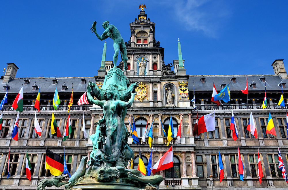 Stadhuis and Brabo Fountain in Antwerp, Belgium <br /> The centerpiece of Grote Markt square is Stadhuis, a mid-16th century, Renaissance city hall that is decorated with colorful flags. Below the Virgin Mary statue is the Hapsburg coat of arms. This Spanish dynasty ruled central Europe during the 16th and 17th centuries. More interesting is the 1887 statue of hero Silvius Brabo. He liberated sailors from paying tolls after defeating a giant named Druon Antigoon. He is about to throw his enemy&rsquo;s severed hand into the Schelde river. The Flemish word for this is handwerpen. According to legend, this is how Antwerp got its name.