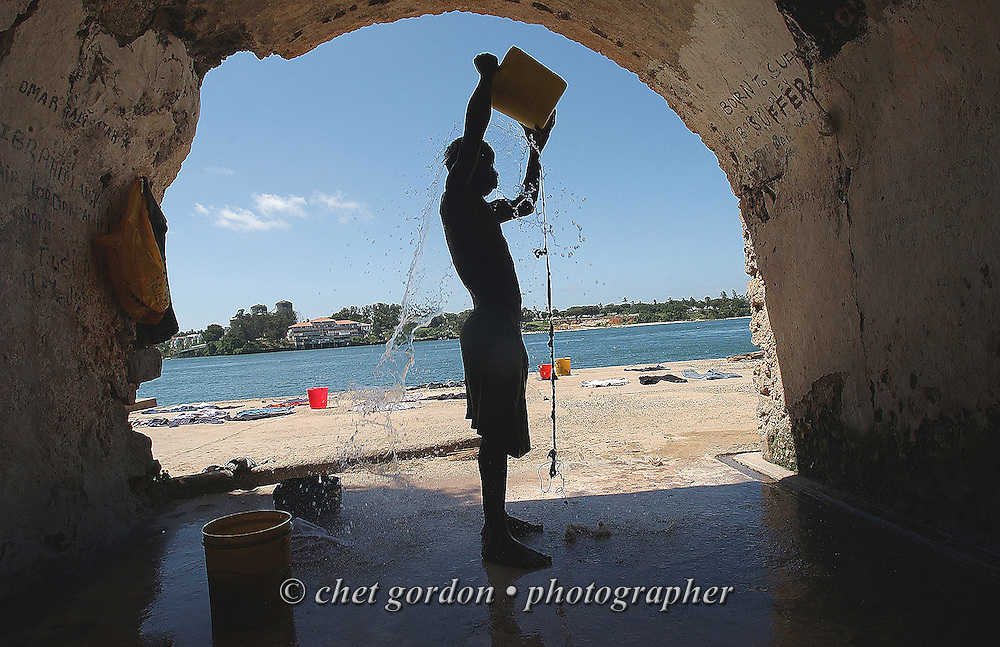 Azman Bakari (32) cools off with water from a fresh water well in the Old Town neighborhood of Mombasa, Kenya on Tuesday, May 23, 2006. The fresh water well built in 1570 AD, filters sea water from the Indian Ocean through rock coral and sunlight, providing Old Town residents a place to do laundry and cool off.
