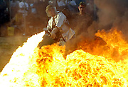 A man fires a rental military flame thrower shooting napalm at a car during the Knob Creek Machine Gun Shoot near West Point, Kentucky April 10, 2005. Thousands of machine gun and military hardware enthusiasts attended the event held each year over weekends in the spring and fall.